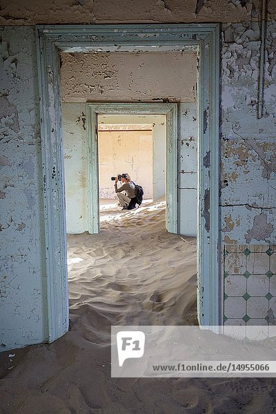 Photographer seen through doorway in Kolmanskop Ghost Town - Luderitz  Namibia  Africa.