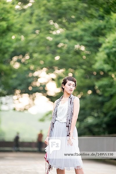Asian female model poses for pictures in the cityscape.