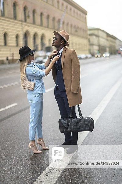 Woman fixing tie of man  Munich  Germany.