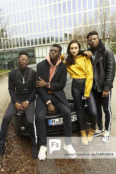 Cool fashionable friends gang leaning against car in city  youth culture in Munich  Germany