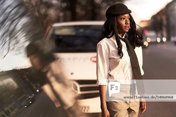 Stylish business woman wearing retro outfit at street walking between cars  African Angolan descent  in city Munich  Germany.