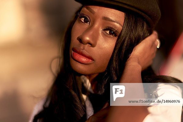 Headshot of stylish woman at street at evening light  sensual mood  African Angolan descent  in city Munich  Germany.