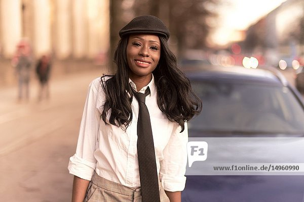 Stylish woman walking in streets in evening sunlight  wearing retro outfit  business look  African Angolan descent  in city Munich  Germany.