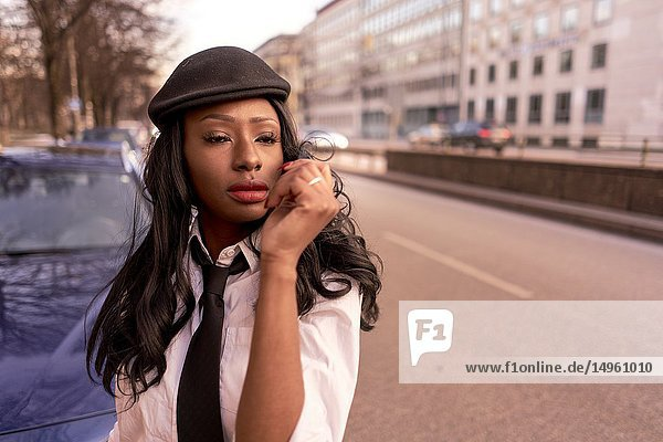 Stylish emotional woman in evening sunlight at street  wearing retro business outfit  individual look  African Angolan descent  in city Munich  Germany.