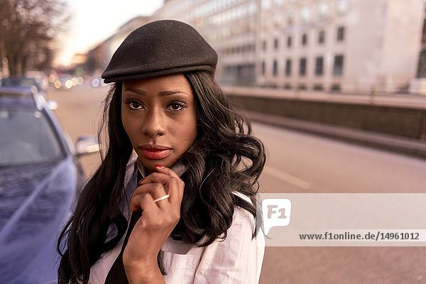 Stylish woman in evening sunlight at street  individual look  African Angolan descent  in city Munich  Germany.