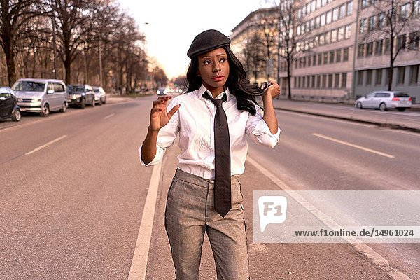 Stylish woman in evening sunlight at street  wearing retro business outfit  individual look  African Angolan descent  in city Munich  Germany.