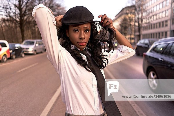 Stylish woman in evening sunlight at street next to traffic  wearing retro clothes  business look  African Angolan descent  in city Munich  Germany.