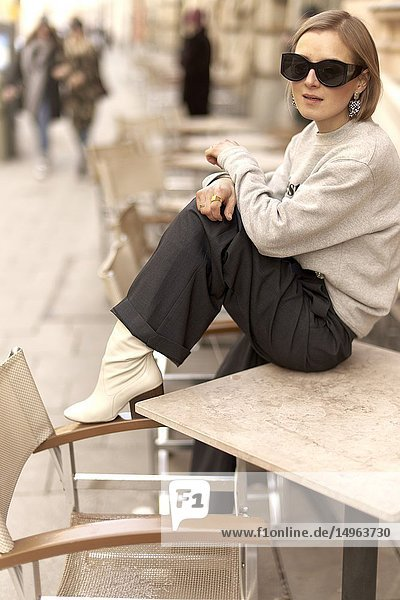 Fashionable blogger woman sitting on table of street café outdoors  streetstyle  in Munich  Bavaria  Germany.