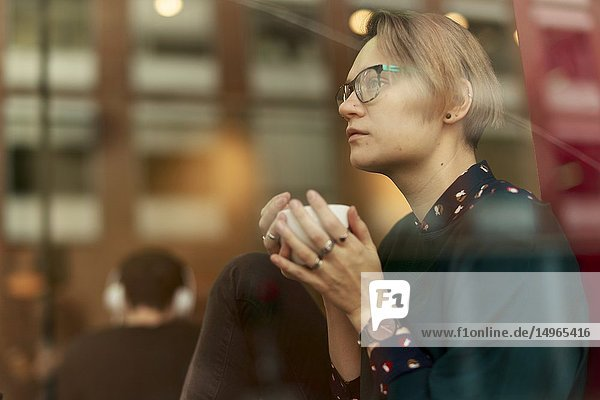 Woman with coffee cup indoors behind glass window in café  in Munich  Germany.