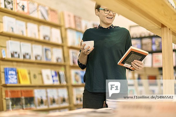 Laughing woman holding book and coffee cup indoors in book store café  happy  in Munich  Germany.