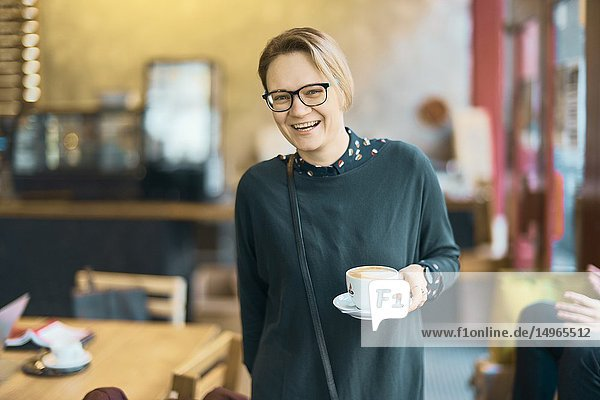 Laughing woman holding coffee cup indoors in café  happy  in Munich  Germany.