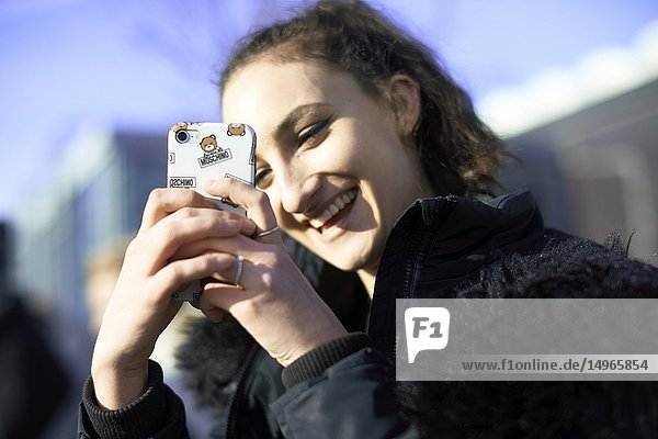 Young woman taking photo with smartphone  in Munich  Germany.