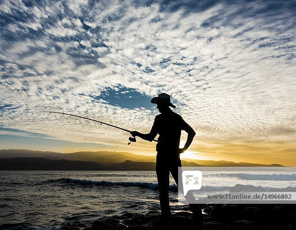Las Palmas  Gran Canaria  Canary Islands  Spain. Man fishing on the north coast of Gran Canaria at sunset. Model released.
