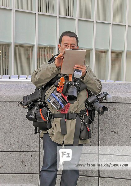 Osaka  Japan - 2010: a photographer carrying multiple cameras and pouches.