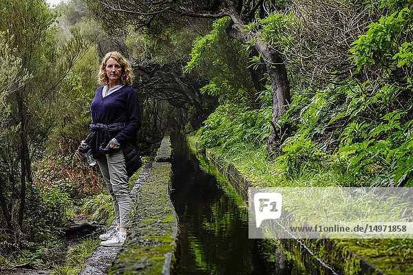 Levada 25 fountains  Rabacal  Madeira  Portugal A woman hiker on this famous 5 kilometer walk along levadas to waterfalls in pristine wilderness.