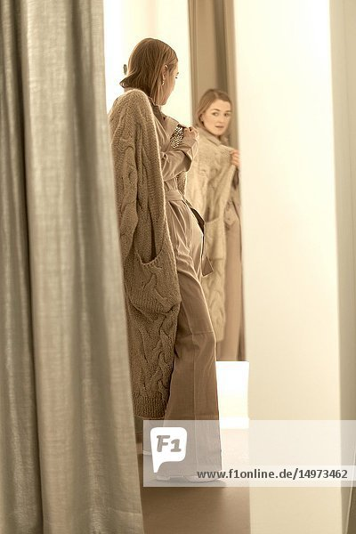 Fashionable woman checking her beige jumpsuit outfit in mirror of fitting room in clothing store  shopping women's fashion trends  in Munich  Germany.