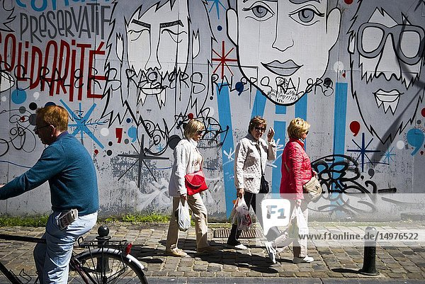 Pedestrians walk past a graffited wall.