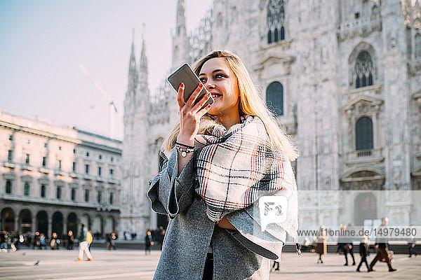 Junge Touristin im Gespräch am Smartphone am Mailänder Dom  Mailand  Italien