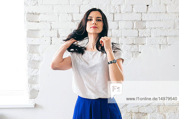 Woman touching hair in front of white brickwall
