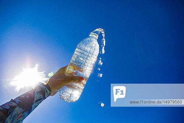 Frau hält Wasserflasche gegen die Sonne