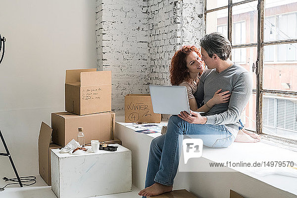 Romantic couple moving into industrial style apartment  sitting on window ledge with laptop