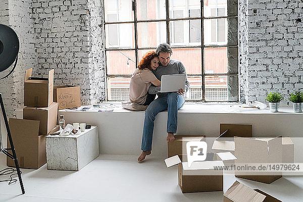 Romantisches Paar zieht in eine Wohnung im Industriestil  sitzt auf einem Fensterbrett und schaut auf einen Laptop