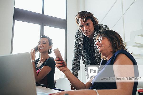 Businesswomen using smartphone and working in loft office
