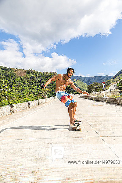 Mann fährt Skateboard auf der Strasse  Pagudpud  Ilocos Norte  Philippinen