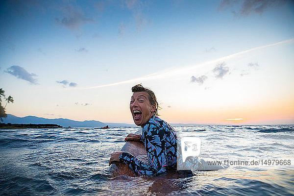 Surfer  der bei Sonnenuntergang im Meer gleitet  Pagudpud  Ilocos Norte  Philippinen