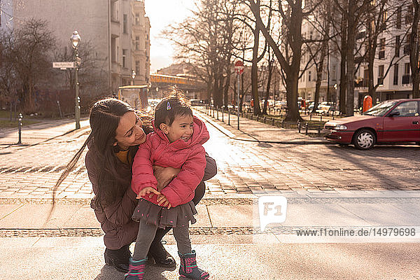 Mother and daughter on pavement