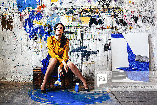 Woman posing in front of wall with graffiti