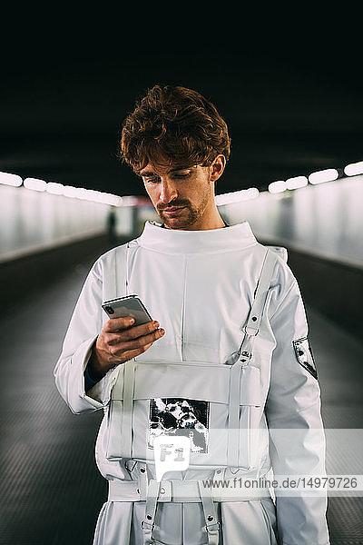 Astronaut mit Smartphone auf überdachter Brücke