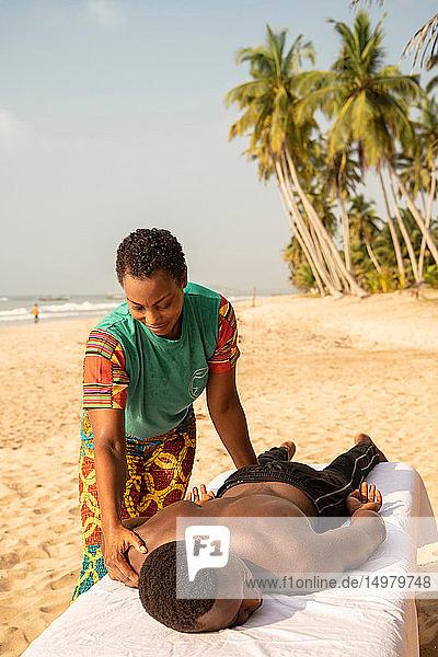 Woman massaging man on beach