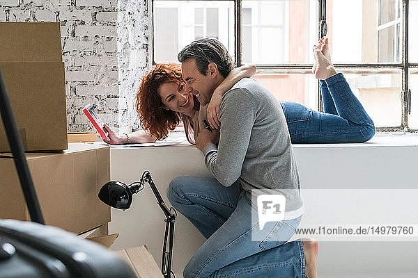 Couple moving into industrial style apartment  on window ledge laughing