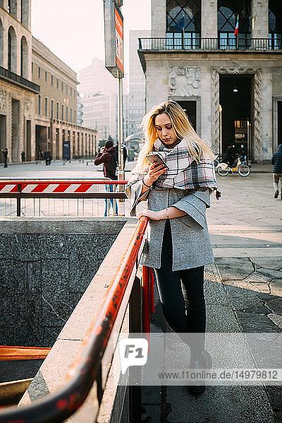Junge Frau an U-Bahn-Station mit Blick auf Smartphone  Mailand  Italien