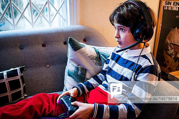 Junge sitzt auf dem Sofa  trägt ein Headset und benutzt den Game-Controller