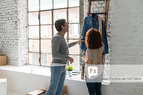 Couple moving into industrial style apartment  looking at denim shirt