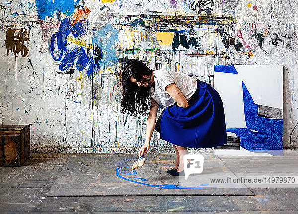 Woman painting on floor in front of wall with graffiti