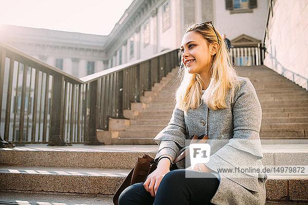 Junge Frau mit langen blonden Haaren sitzt auf einer Treppe  Mailand  Italien