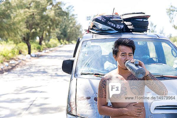 Mann trinkt vor einem auf der Straße geparkten Fahrzeug  Pagudpud  Ilocos Norte  Philippinen
