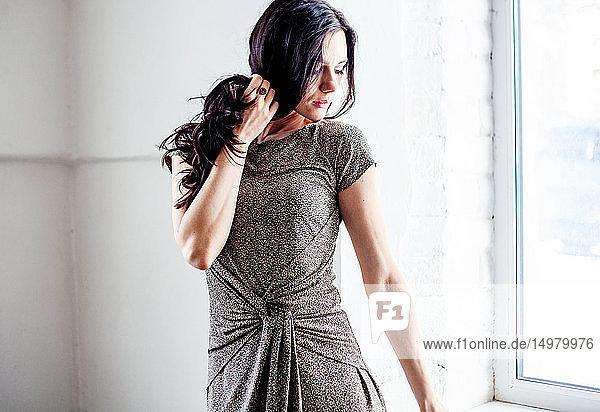 Woman holding hair  posing beside window