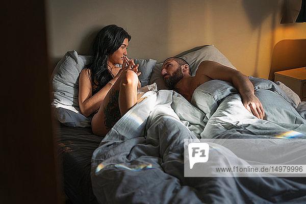 Hipster-Paar im Bett liegend