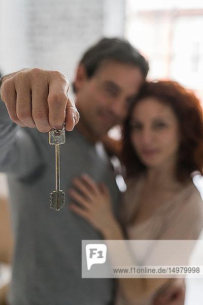 Couple moving into apartment holding key  shallow focus portrait