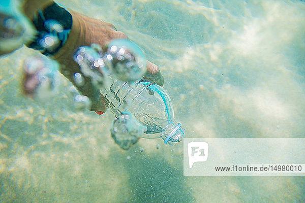 Frau füllt Plastikflasche mit Meerwasser