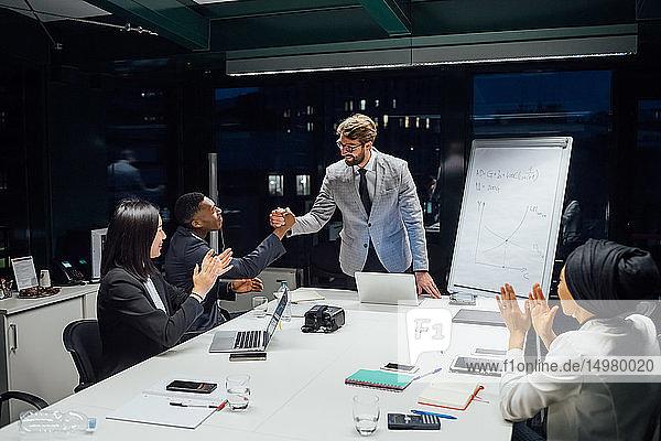Geschäftsleute schütteln Hände und klatschen bei Büropräsentation