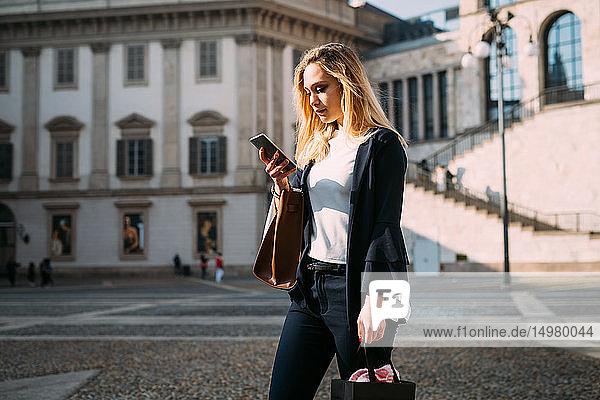 Junge Touristin mit Smartphone auf dem Stadtplatz  Mailand  Italien