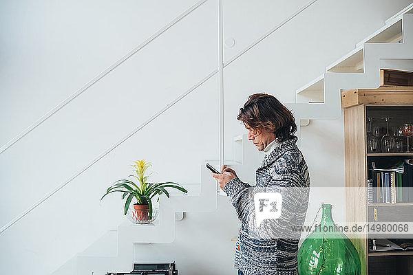 Man using smartphone in loft office