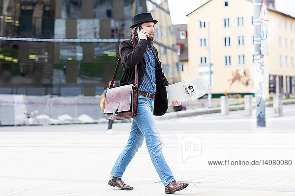 Male skateboarder strolling in city square making smartphone call  Freiburg  Baden-Wurttemberg  Germany