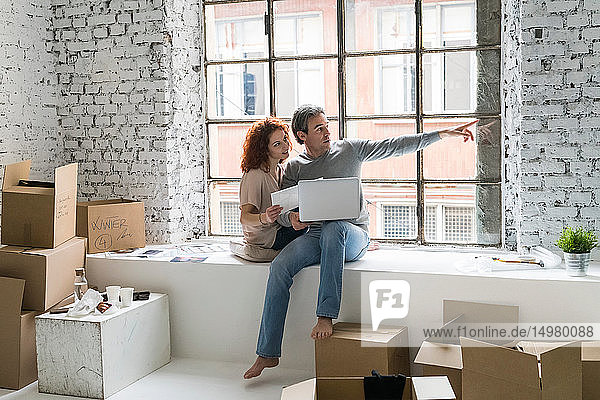 Couple moving into industrial style apartment  sitting on window ledge pointing