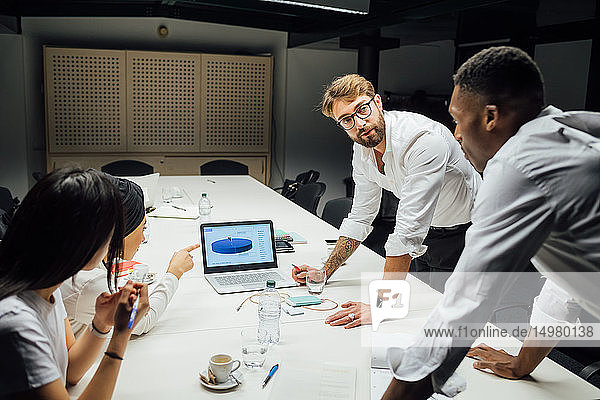 Geschäftsmänner und -frauen diskutieren am Konferenztisch